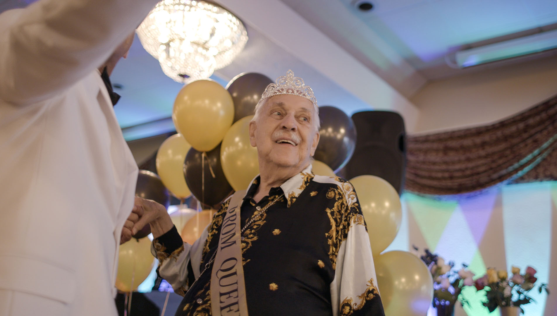 """An elderly gentleman celebrates """"prom"""" while in an assisted living facility, wearing sash and crown"""