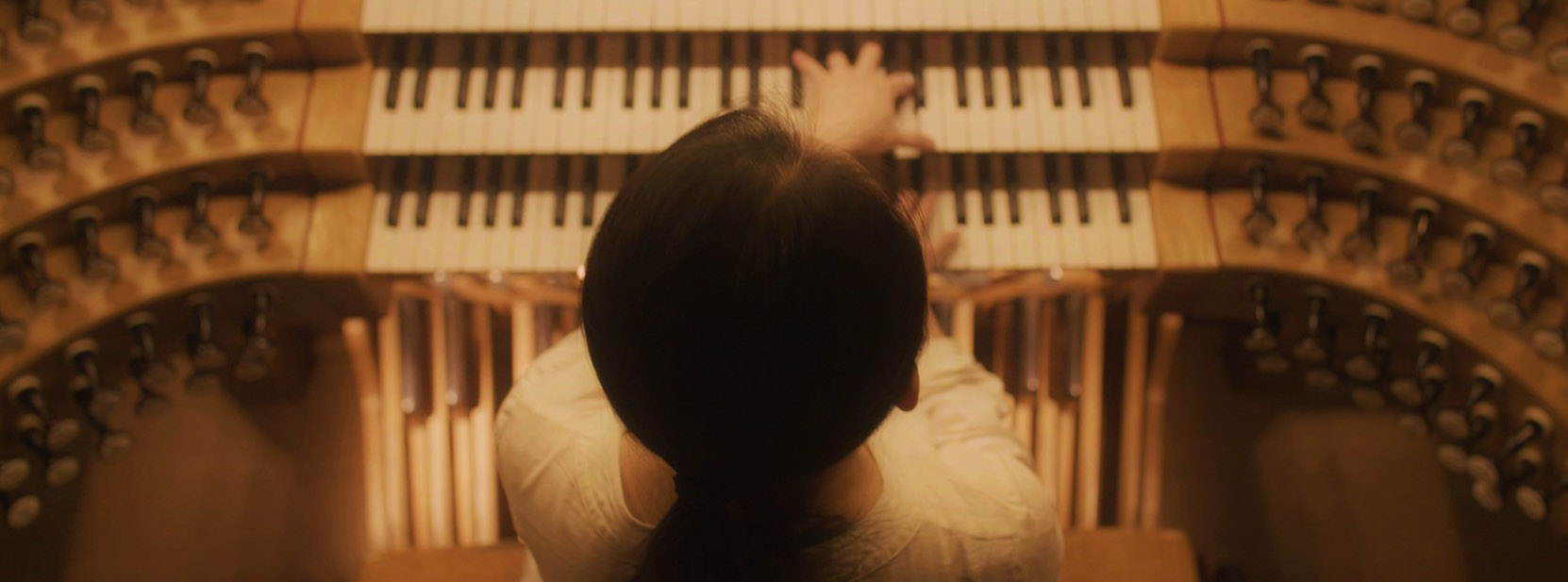 view of back of woman playing pipe organ